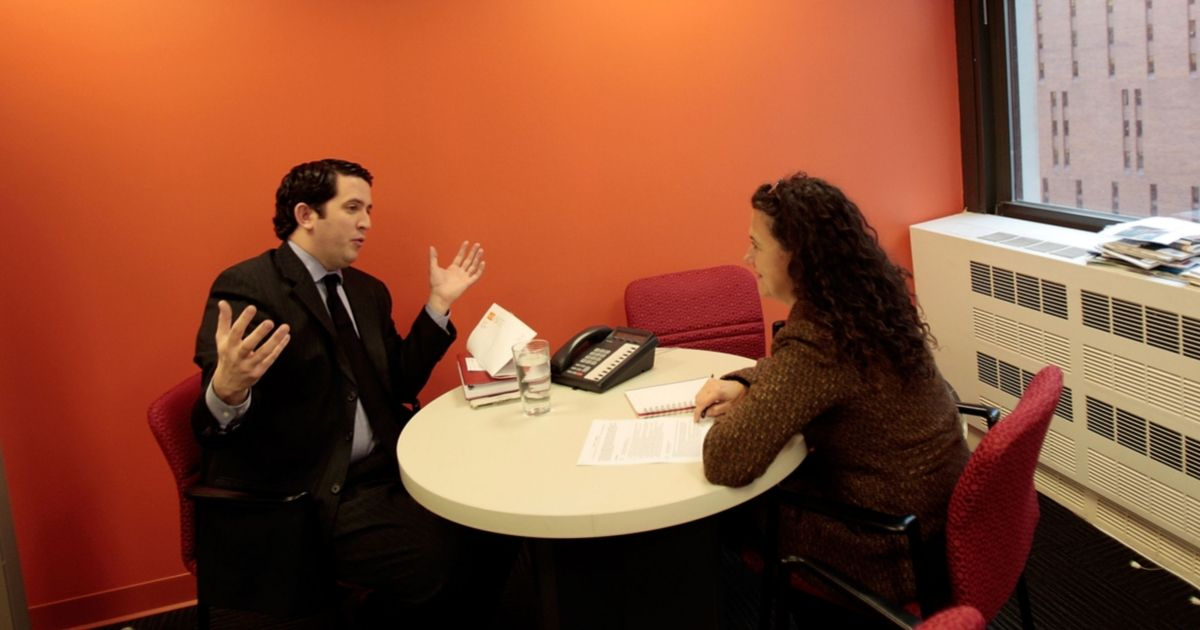Two people sit at a round table in an orange office having a job interview meeting.
