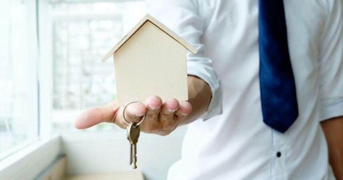 A person hold a replica of a home and a pair of keys in the palm of his hand