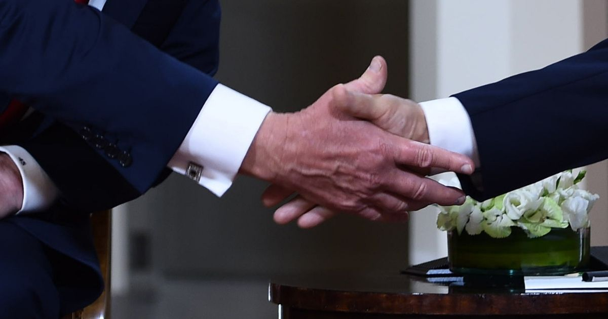 A close up picture of Donald Trump shaking hands with Vladimir Putin