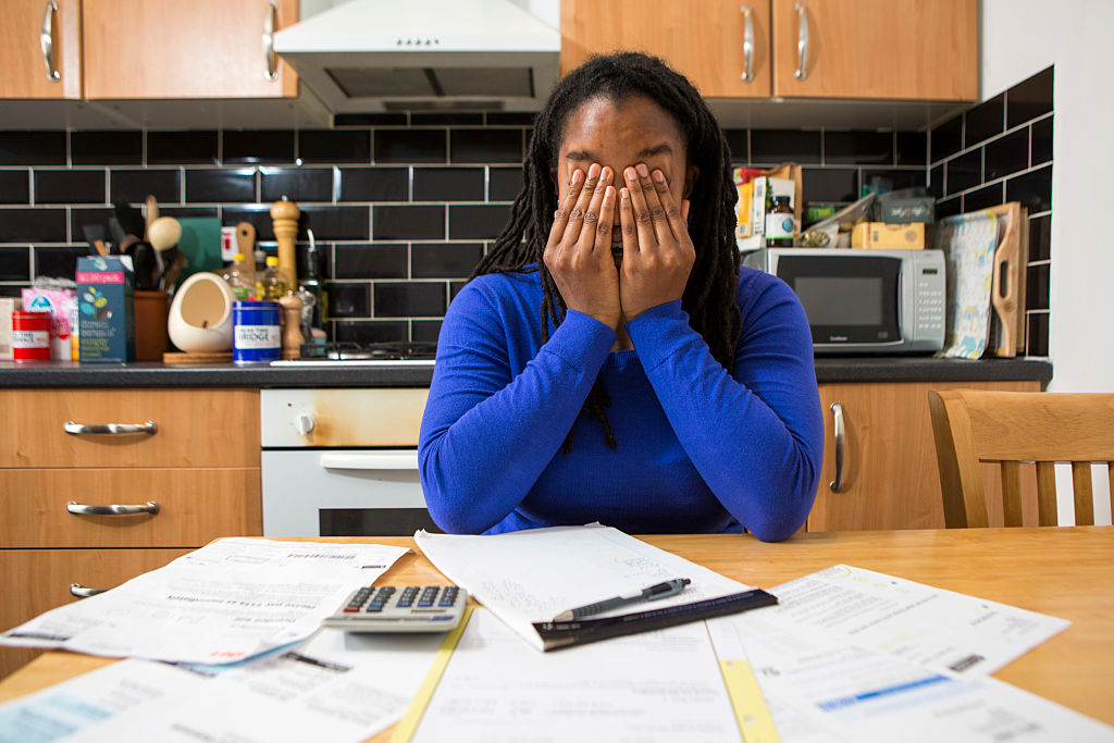 A young lady sits at her kitchen table at home checking over the household bills.
