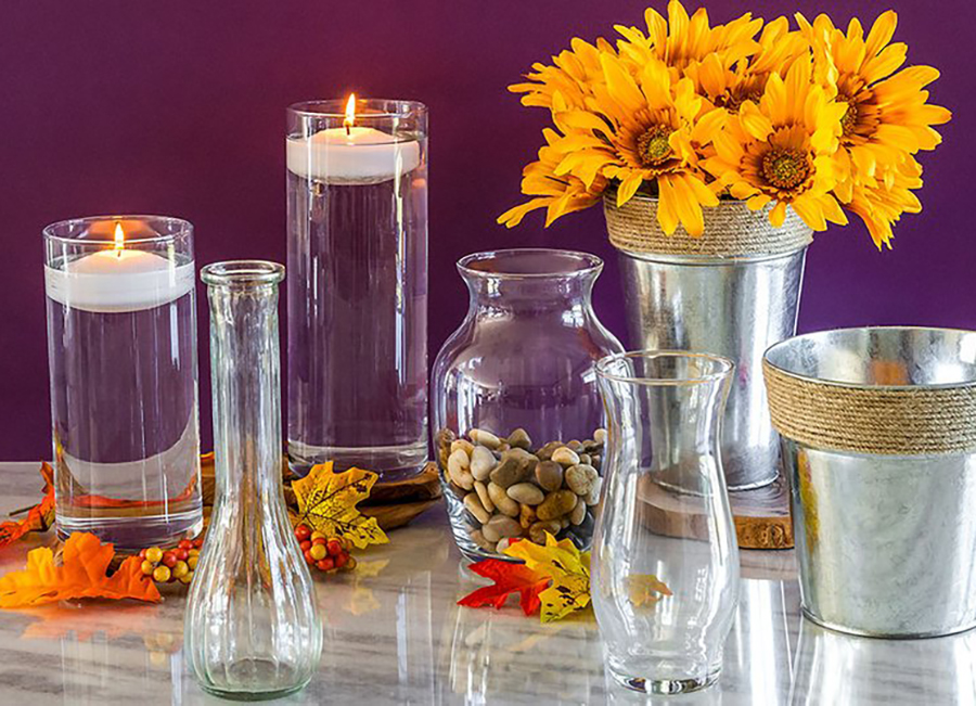 Glass vases from Dollar Tree hold artificial flowers and candles.
