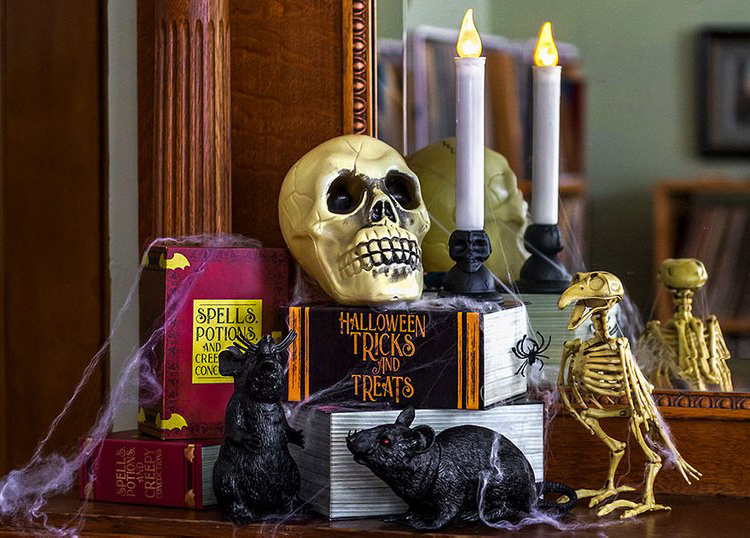 Halloween decorations are stacked on a desk with a mirror behind them.