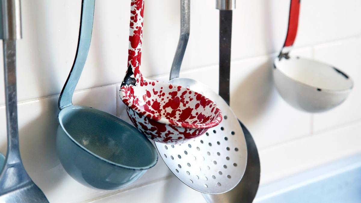 Kitchen utensils hang against a white-tile wall.