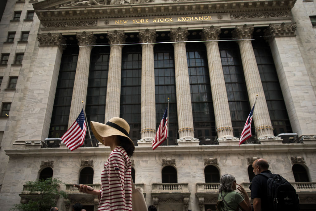 A woman walks past the New York Stock Exchange (NYSE)