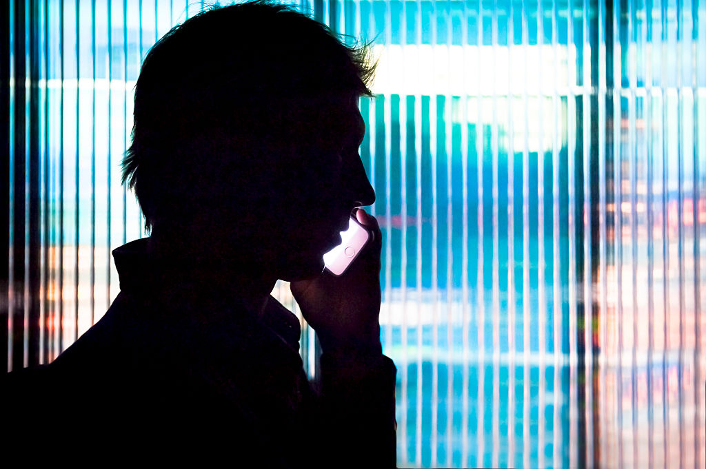 Silhouette of a man talking on a cell phone