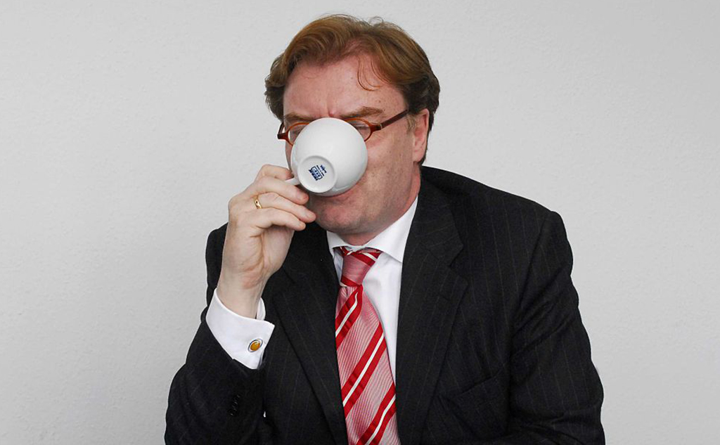 Man drinking coffee in suit