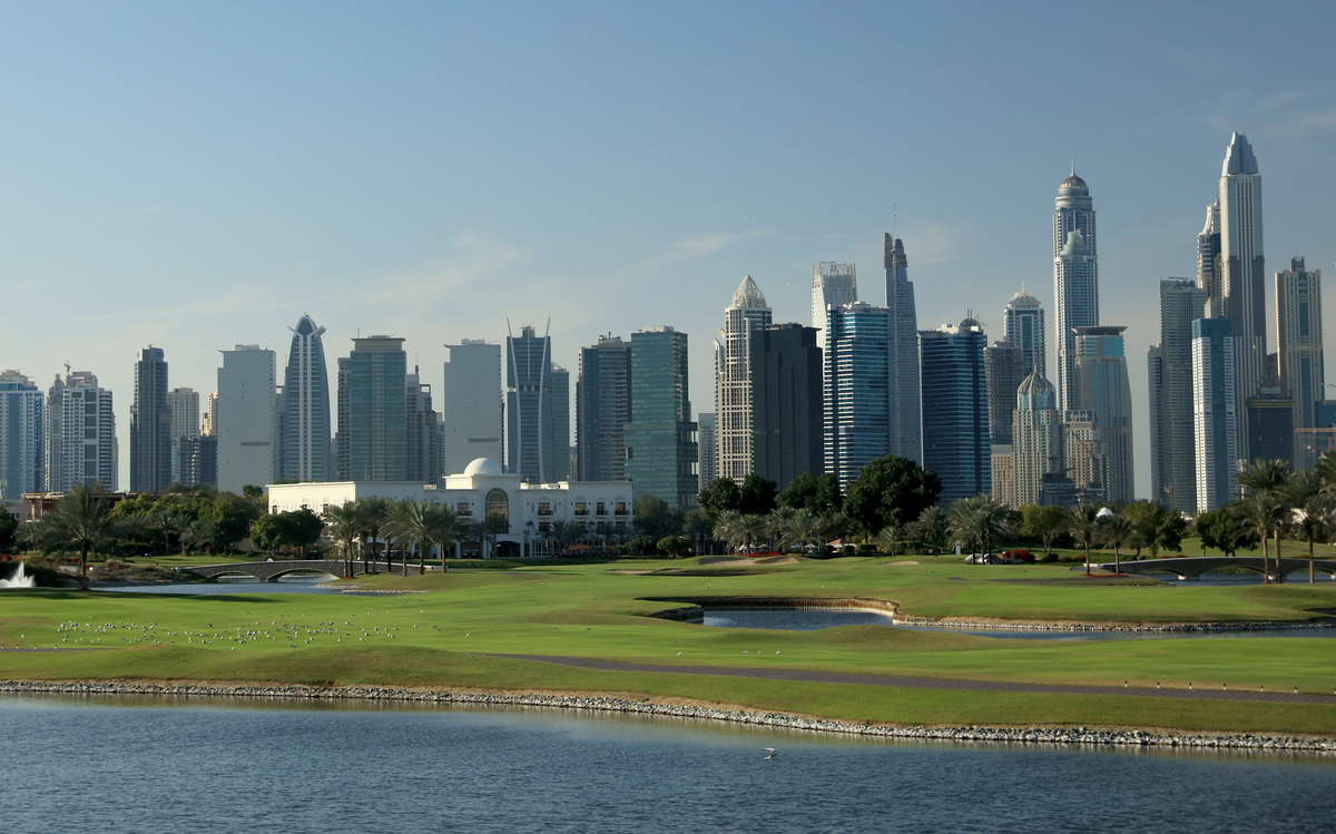 View of the 18th hold at The Adress Montgomerie Golf Club features the city of Dubai in the background.