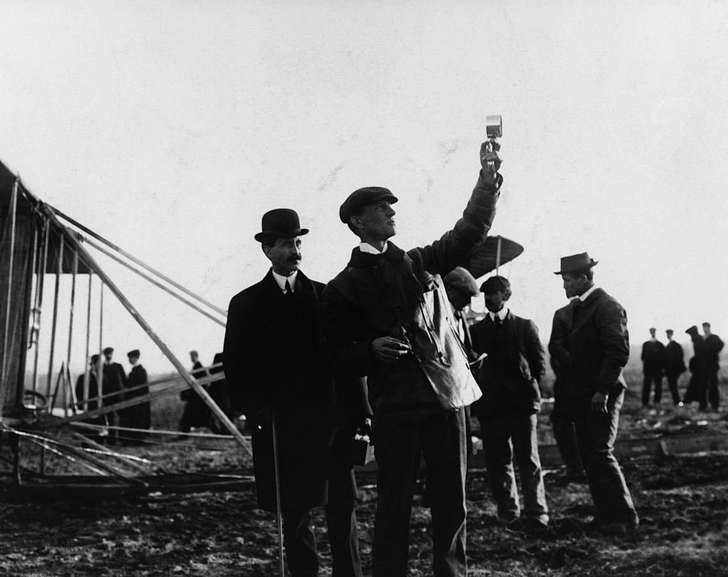 Picture of the Wright Brothers with Orville watching Wilbur take readings outdoors,