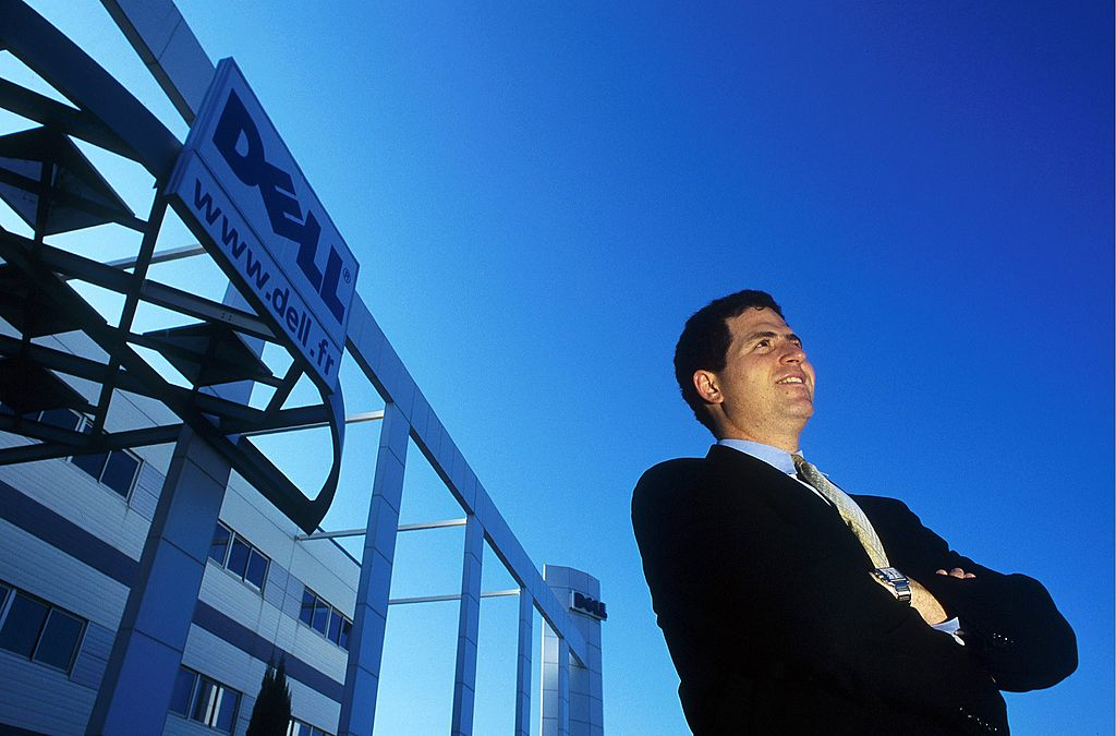 michael dell standing in front of a building with the dell logo