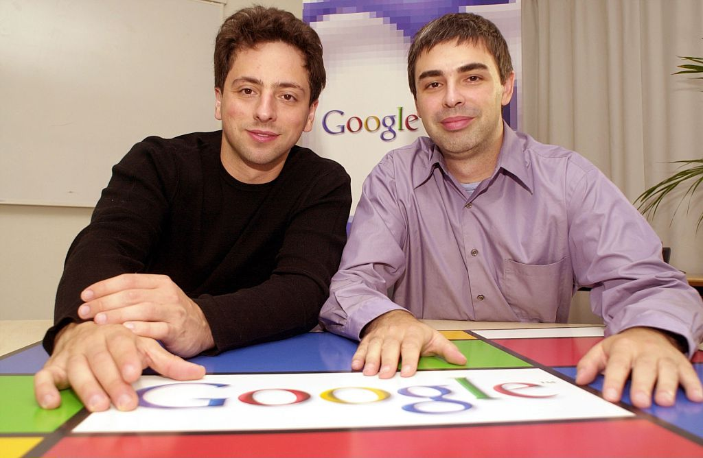 larry page and sergey brin sitting at a table with the google logo