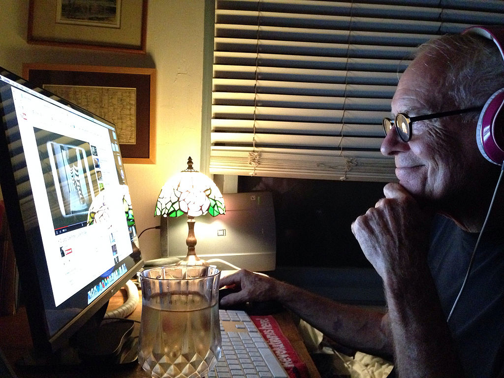 Senior male enjoying Internet music at night