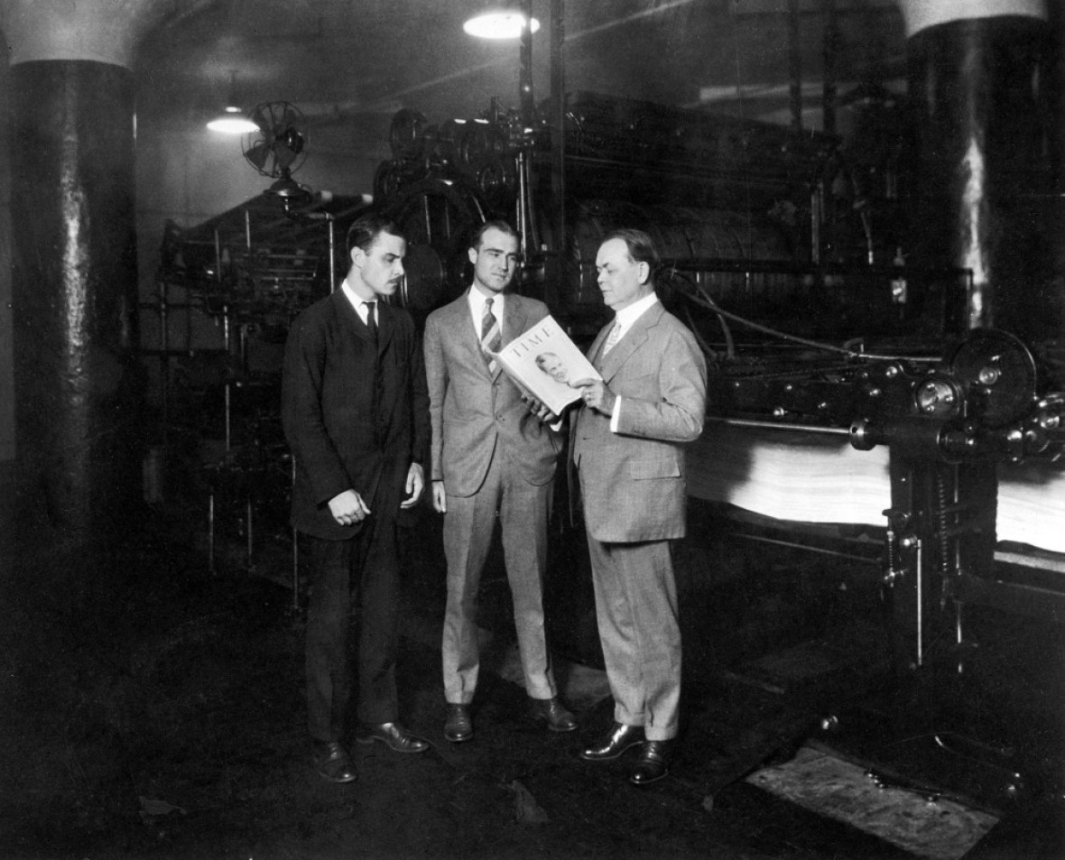 briton hadden and henry luce standing with william r. hopkins holding an issue of time magazine