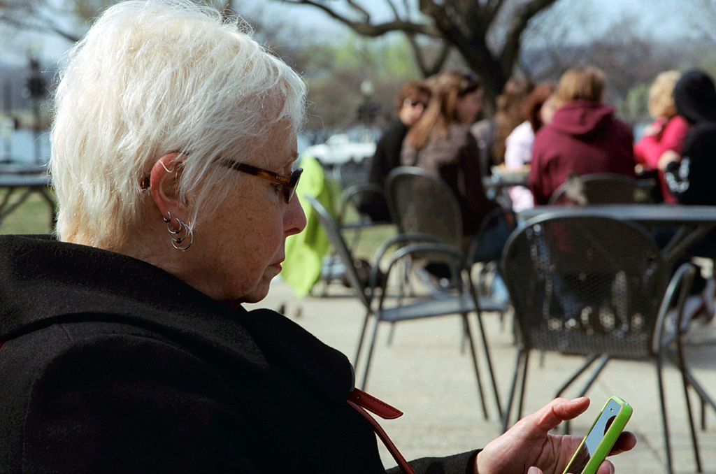 an elderly person using a phone in public