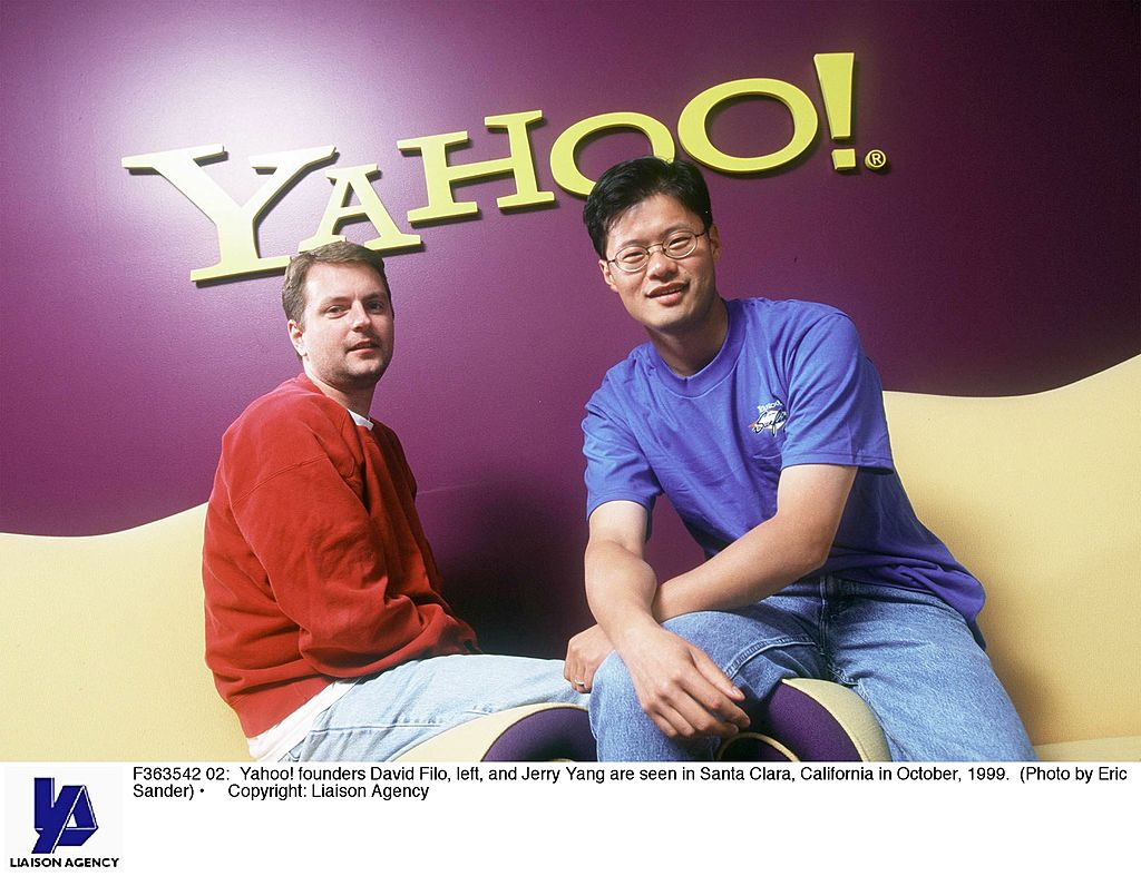 david filo and jerry yang in front of a yahoo! sign
