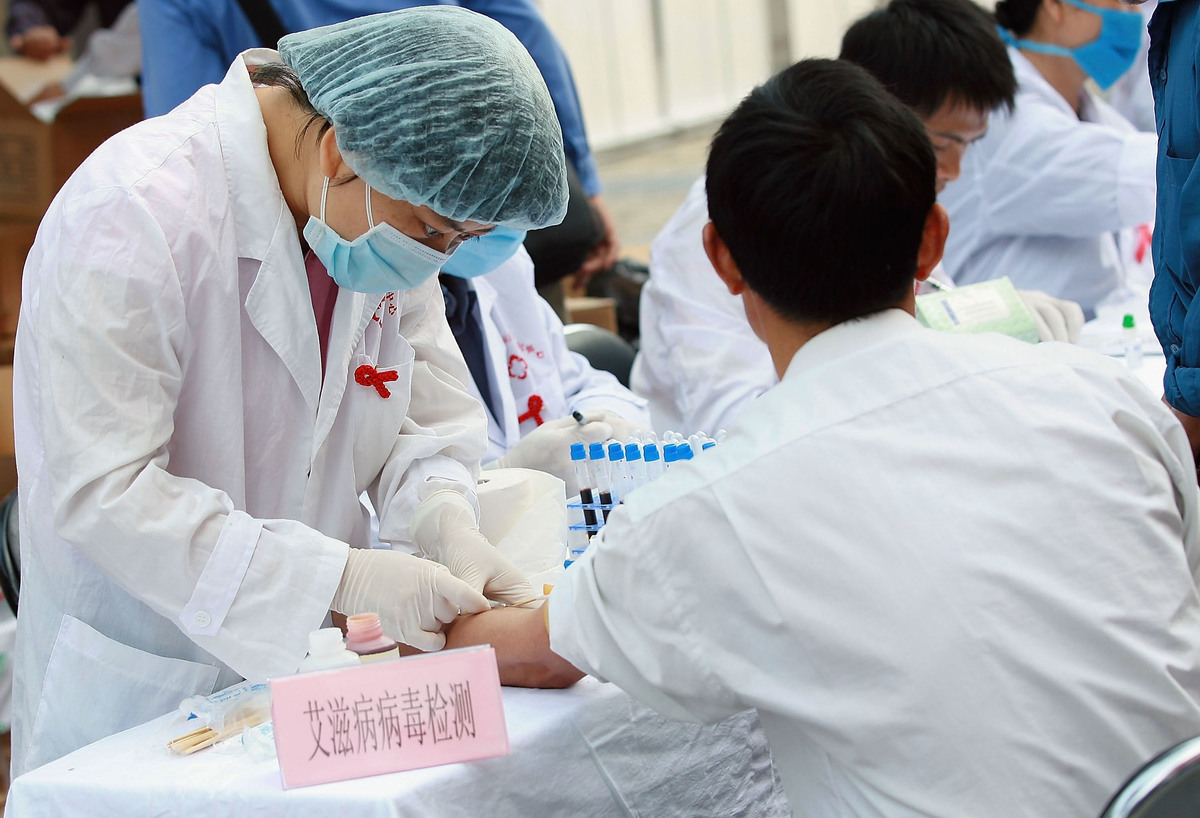 A Chinese doctor collects a local resident's blood sample