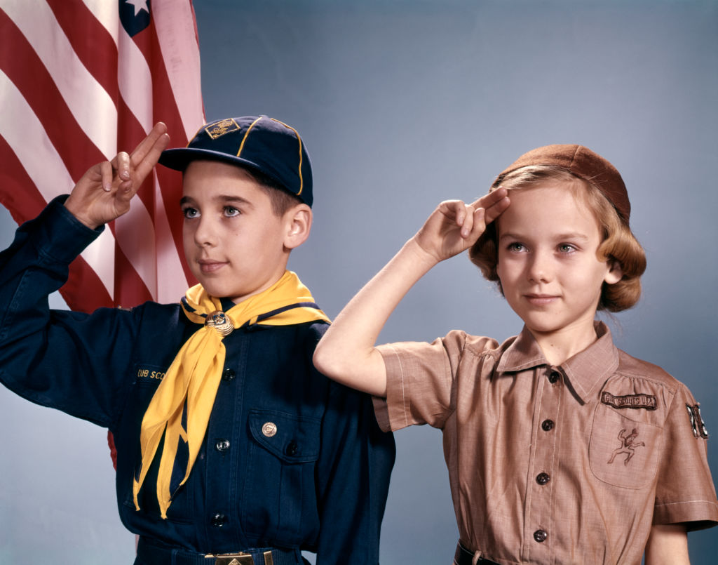 a boy scout and girl scout in their uniforms saluting the american flag