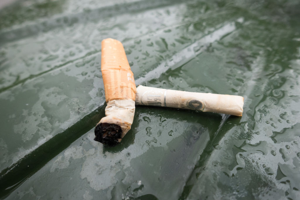 Cigarette buts are seen on top of a public trashcan