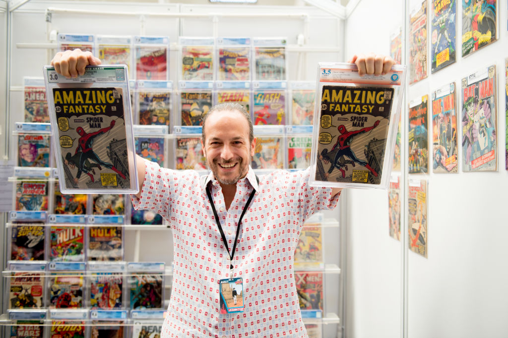 a man holding spider man comic books