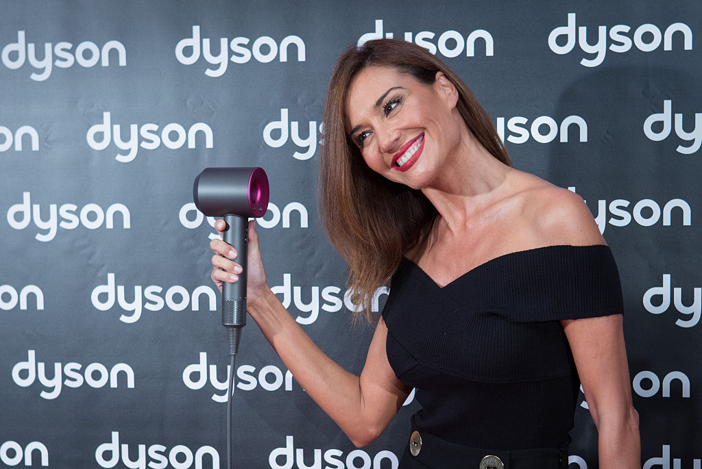 a woman preteding to use a dyson supersonic hairdryer on a red carpet