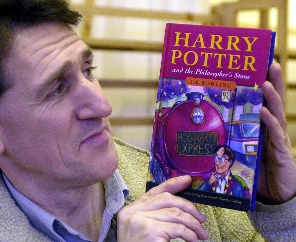 a man holding a first edition copy of harry potter and the philosopher's stone