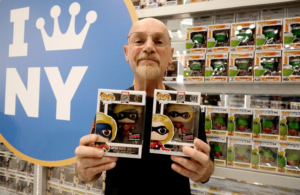 jim starlin posing with two funko pop! figurines with more in the background