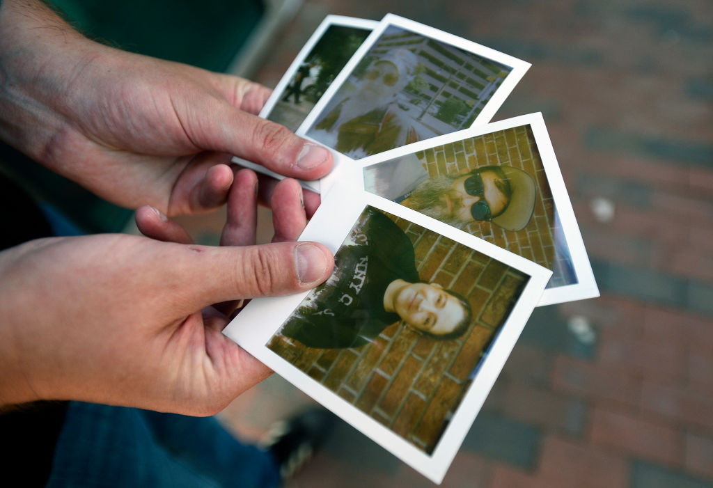 someone holding 4 instant photos they took of people
