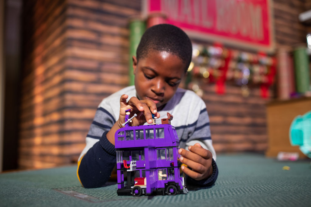 a boy playing with a harry potter lego set