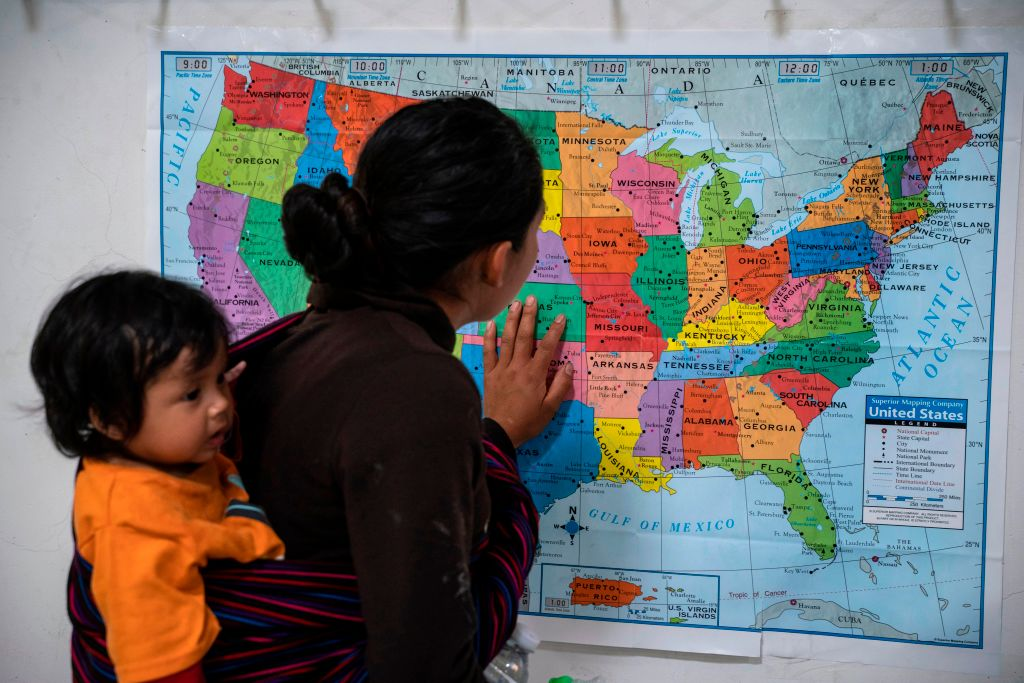 a woman and her baby looking at a map of the united states