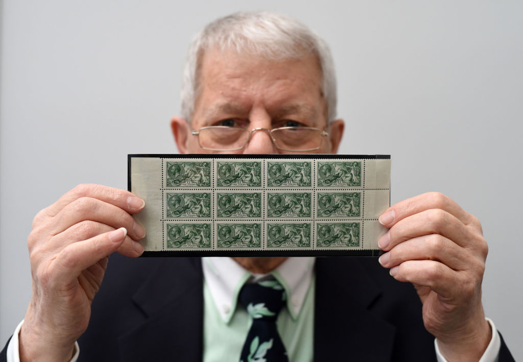 a stamp dealer holding a collection of green stamps