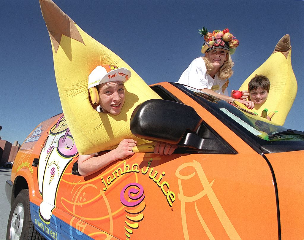 Teens dressed like fruit drive a Jamba Juice car.