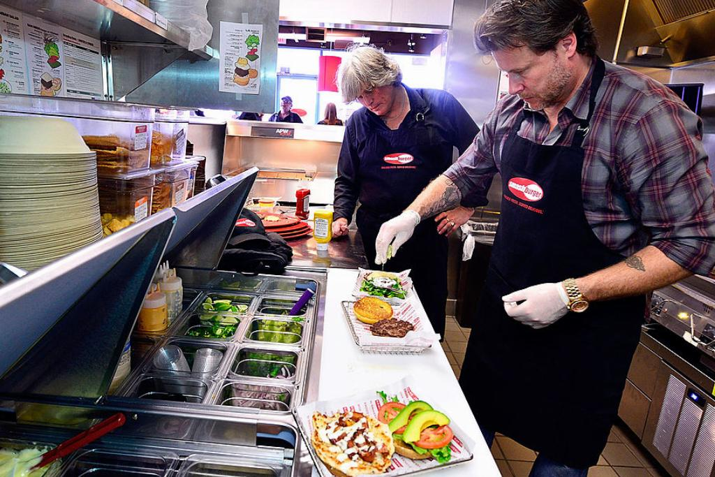 Actor Dean McDermott prepares burgers alongside the founder of Smashburger.