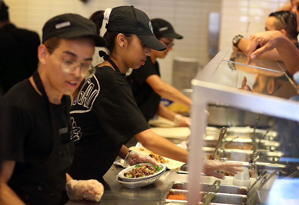 Employees work in an assembly line at Chipotle.