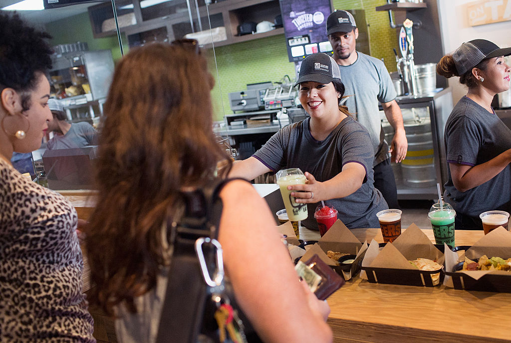 A Taco Bell worker hands beverages to guests.