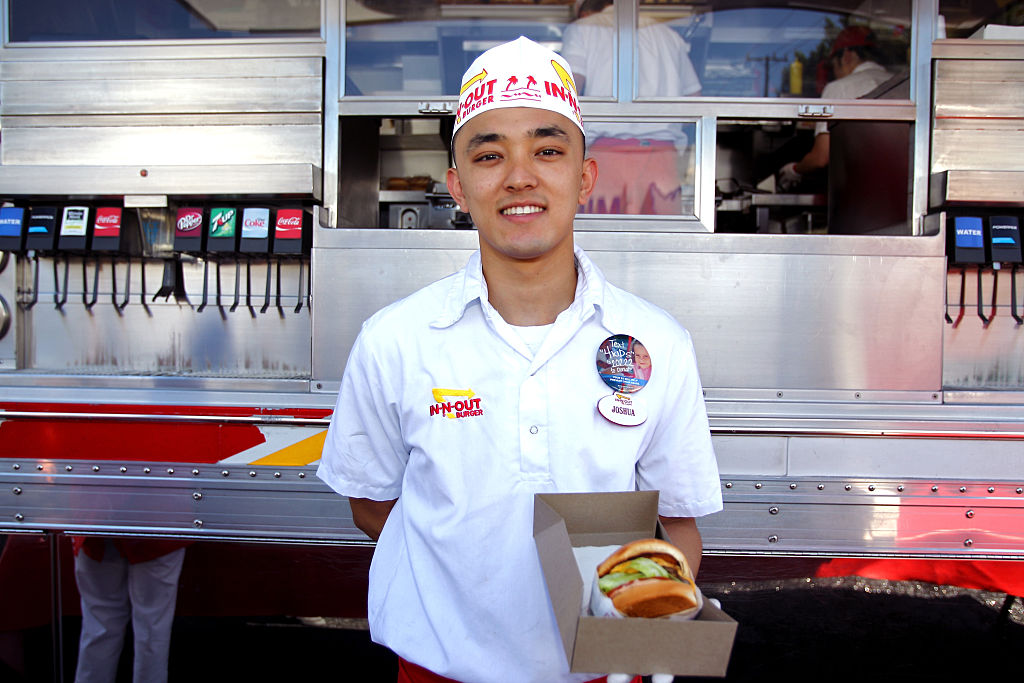 An In-N-Out worker holds a cheeseburger.