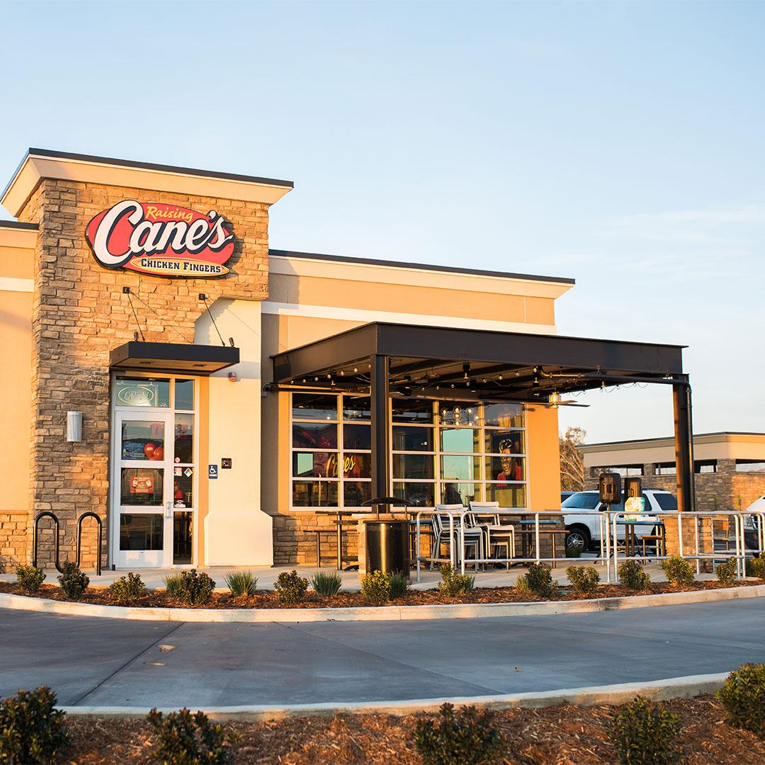 A Raising Cane's building is pictured at sunset.