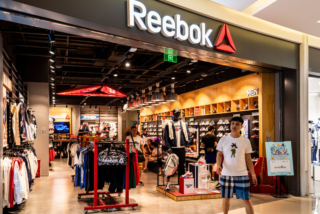 Pedestrian walks past a Reebok store