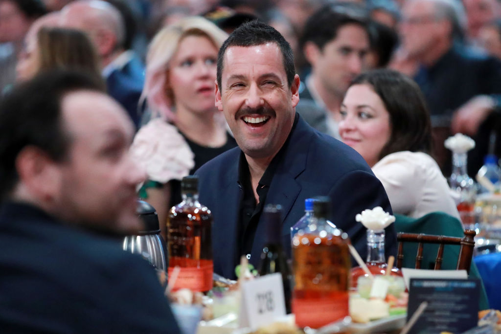 adam sandler with a mustache sitting at a table during an awards show