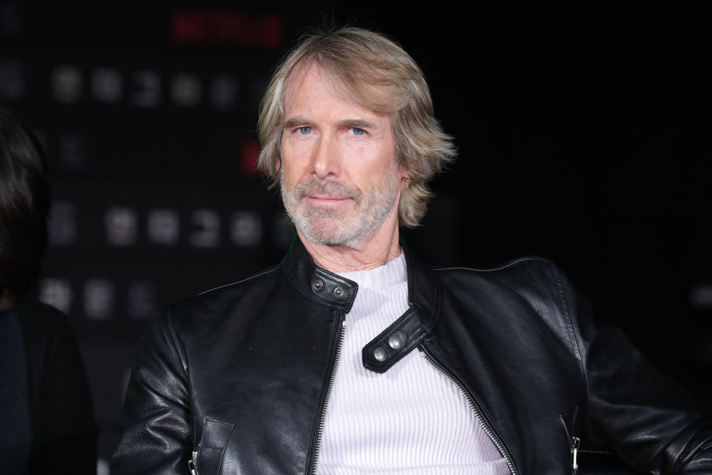 michael bay posing for a photo in a leather jacket