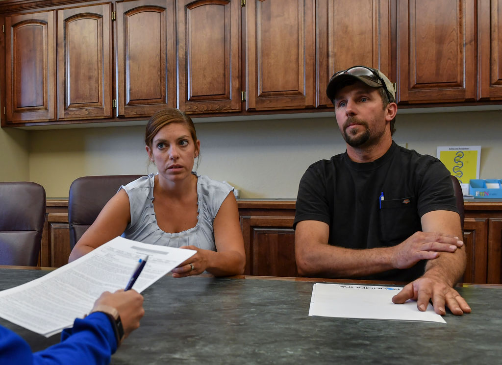 Sarah Krocak and her husband Marty, meet with banker Jill Rynda, left, as the couple got an extension on the repayment