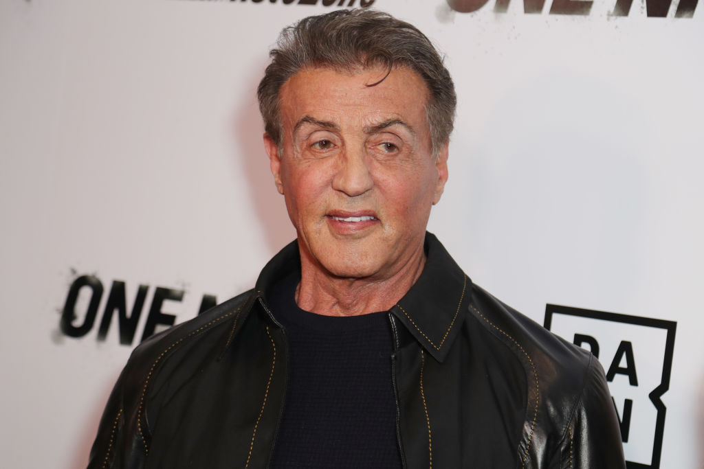 sylvester stallone wearing a leather jacket on a red carpet
