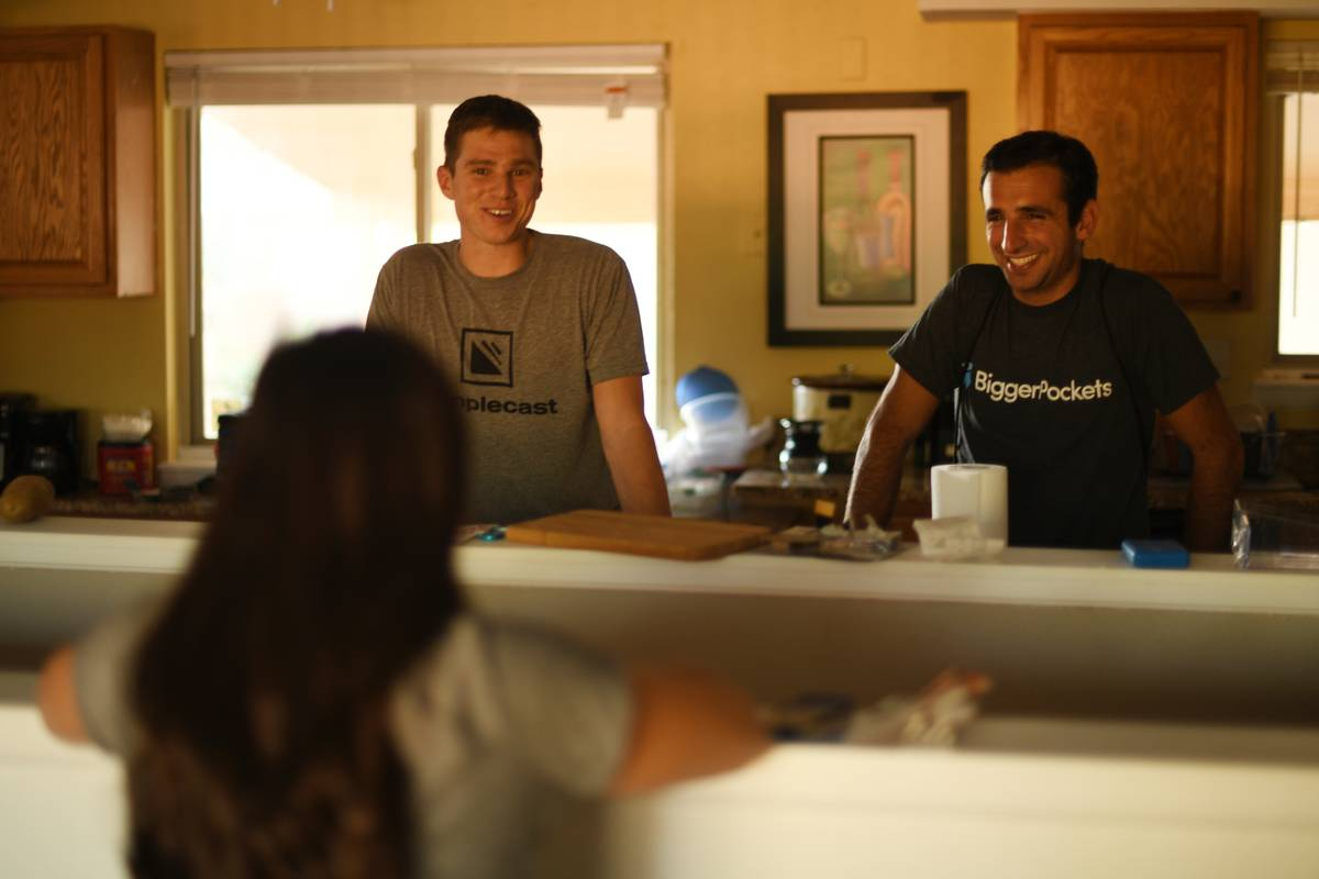 Three apartment rules converse in their kitchen.