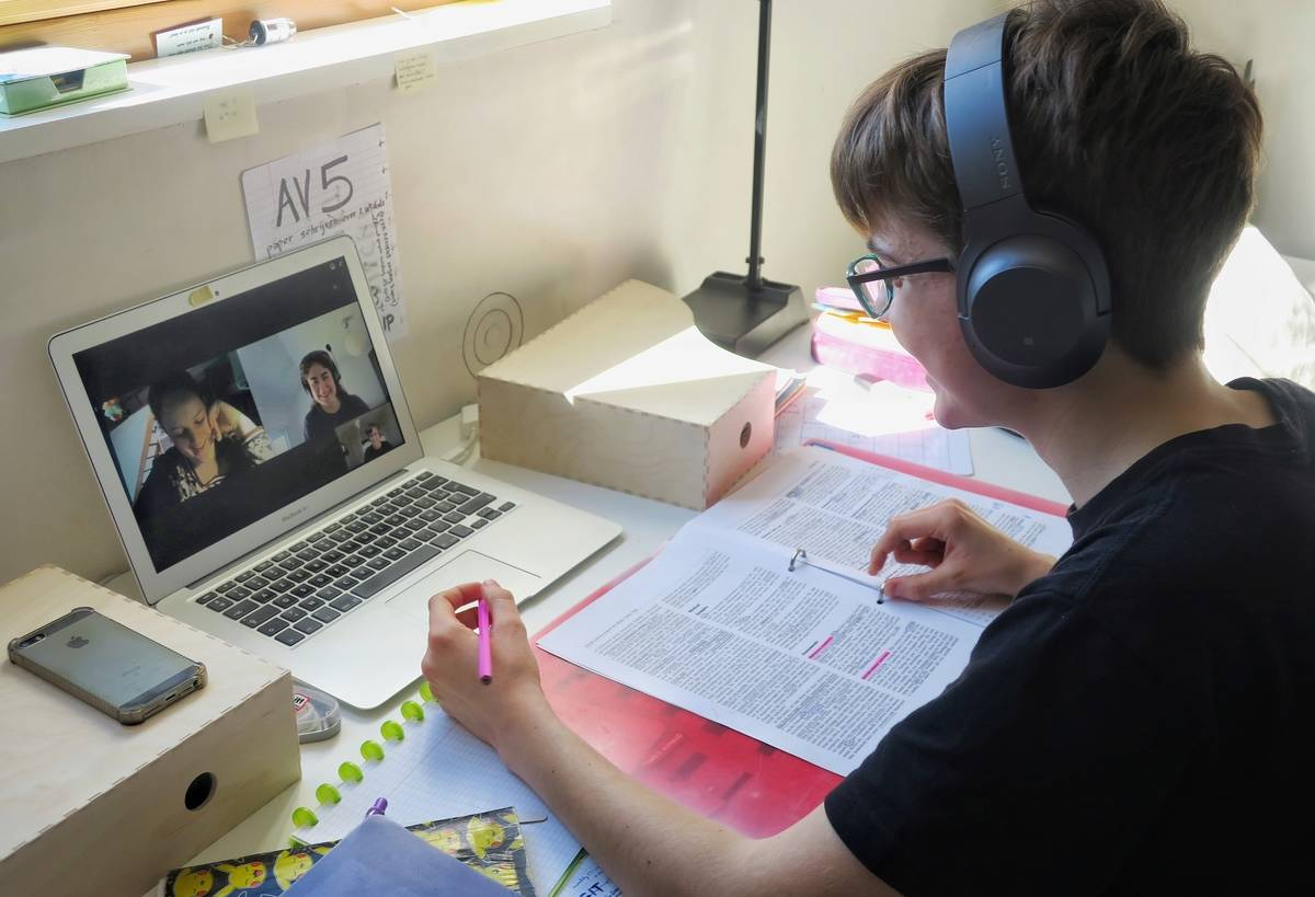 A psychology student studies with two friends over video chat.