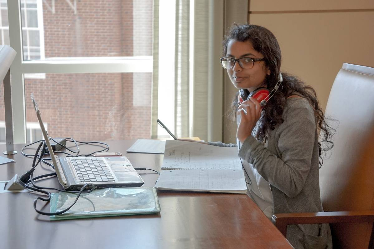 A university student removes her headphones while she studies in a library.