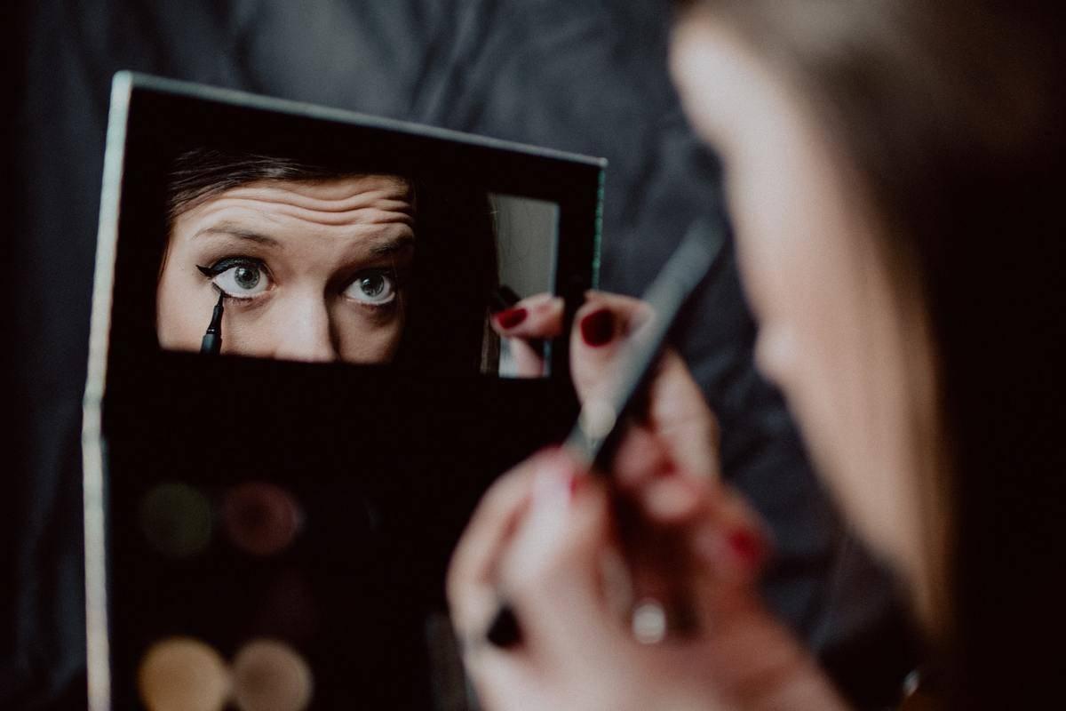 A woman applies makeup using a mirror on an eyeshadow palette.