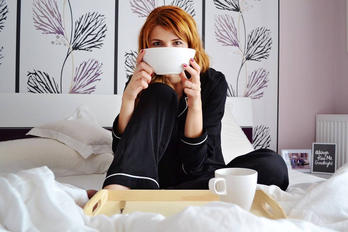 A woman eats cereal and coffee in bed.