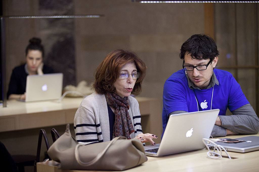 A woman is trained by an Apple employee at the Genius Bar at the Apple Store