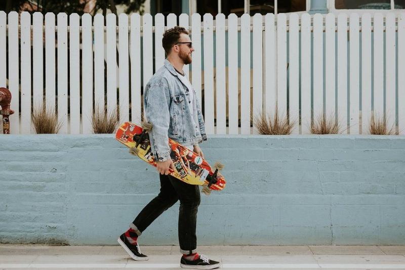 A man walks outside with a skateboard.