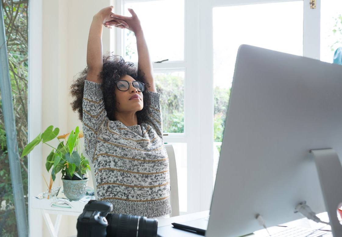 A woman stretches at her computer desk.