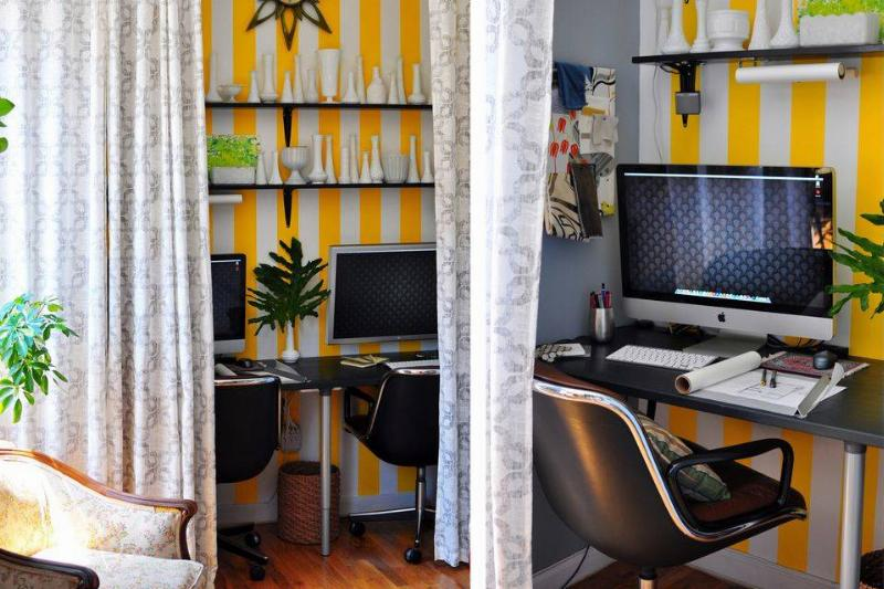A curtain separates an office space from living space.