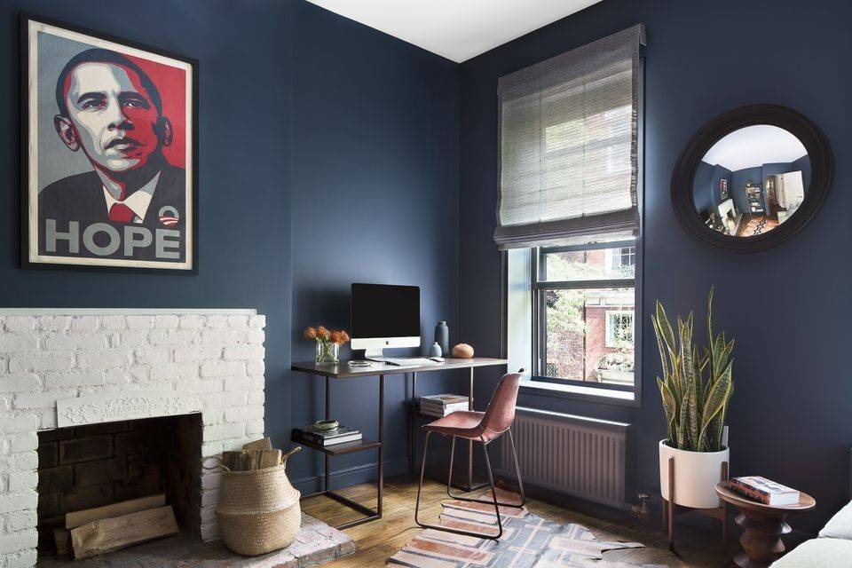 A thin desk and chair sit in the corner of a living room.
